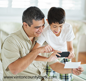 Son And Father Using Mobile Phone To Deposit Check