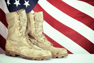 Old combat boots with American flag in the background. Vintage filter effect.