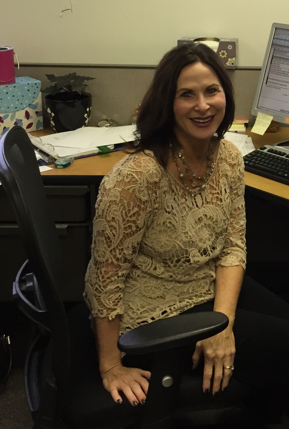 Credit Analyst Karen Householder takes a break from reviewing loan files to pose for a picture.
