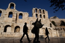 Tourists walk in front of the ancient Herodes Atticus theatre below the hill of the Acropolis in Athens