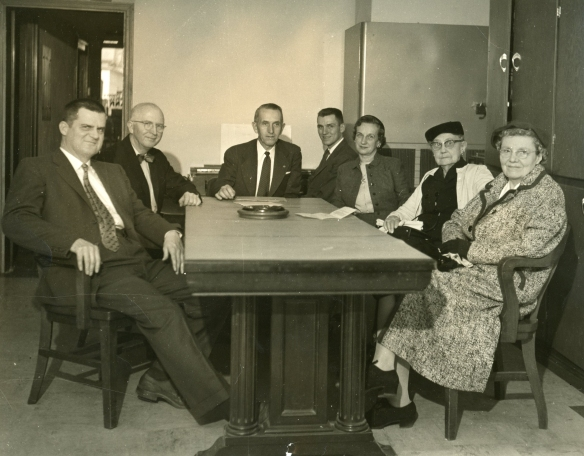 Group with J.G at Board Table sixties era