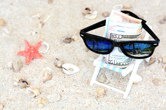 Holiday money concept - Banknotes with sunglasses in a beach chair and sand background