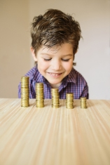 Boy looking at coins on a table